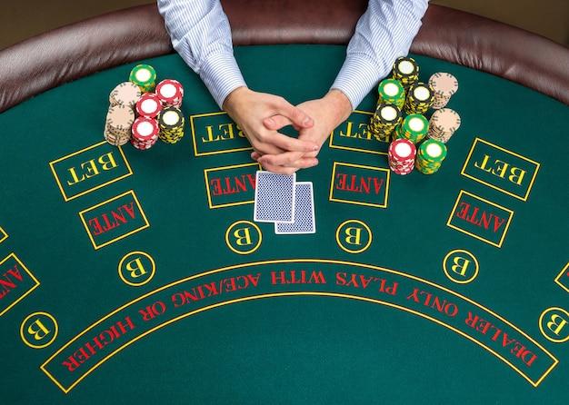Cerca del jugador de póquer con naipes y fichas en la mesa de casino verde, vista desde arriba.