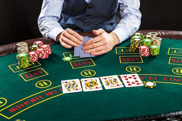 Cerca del jugador de póquer con naipes y fichas en la mesa de casino verde