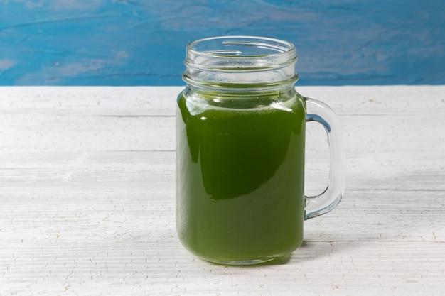Cerca de jugo de apio verde fresco en vidrio