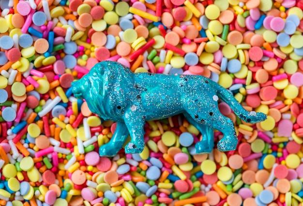 Cerca de un juguete de estatuilla de león azul en una cama de dulce confites dulces