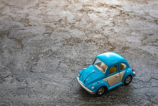 Cerca del juguete un modelo de coche azul sobre un fondo de yeso