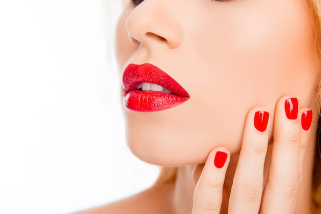 Cerca de labios de mujer sexy con lápiz labial rojo y manicura roja