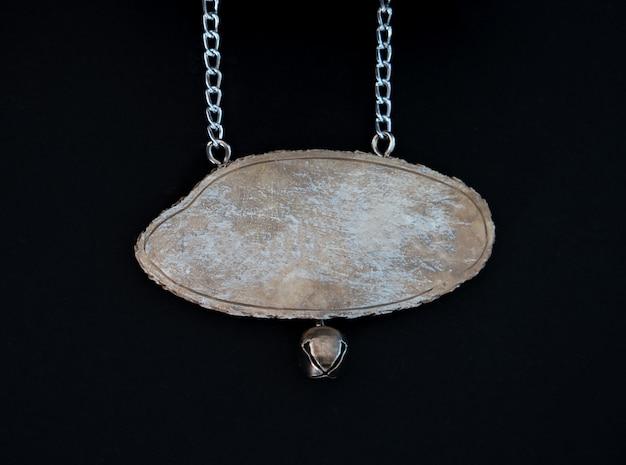 Cerca de un letrero de madera colgando de una cadena de metal sobre negro