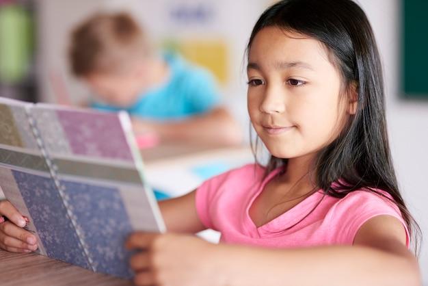 Cerca del libro de lectura de niña de raza mixta