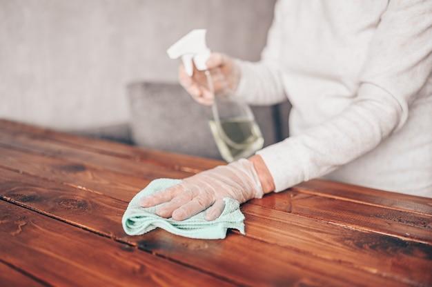 Cerca de la limpieza de la mesa de madera en el hogar, desinfectar la superficie de la mesa de la cocina con una botella de spray antibacteriano desinfectante, lavar las superficies con una toalla y guantes.
