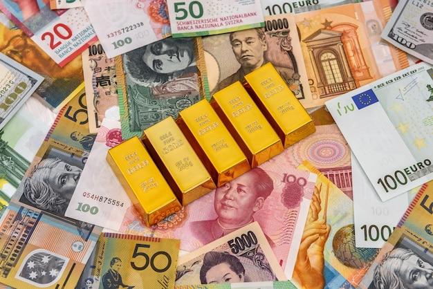 Cerca de lingotes de oro en billetes de colores