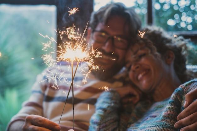 Cerca de la luz de bengala y pareja sonriendo en segundo plano en casa