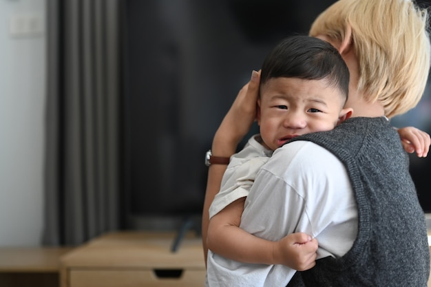 Cerca de la madre asiática sosteniendo a un bebé llorando en un hogar cómodo