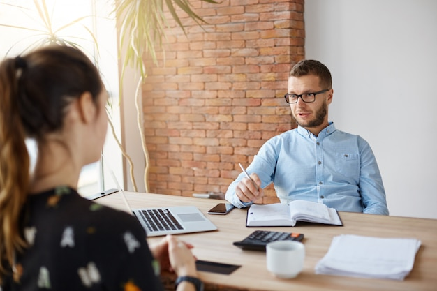 Cerca de maduro director de la compañía barbudo en gafas sentado en la oficina con una chica de pelo oscuro delante de él en la entrevista de trabajo. hombre preguntando a las mujeres sobre la experiencia laboral