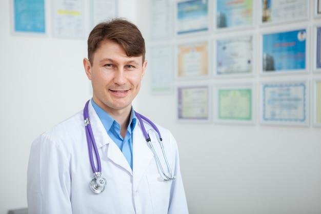 Cerca de maduro médico varón calificado sonriendo, espacio de copia