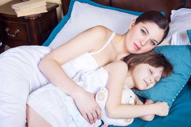 De cerca. mamá mirando a cámara y niño abrazándose y durmiendo juntos. tiro del estudio