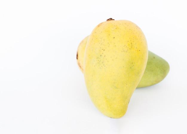 Cerca de mangos frescos sobre fondo blanco.