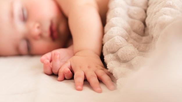 Cerca de la mano adorable bebé
