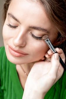 Cerca de la mano del artista de maquillaje aplica polvo de sombra de ojos, maquillaje de ojos.