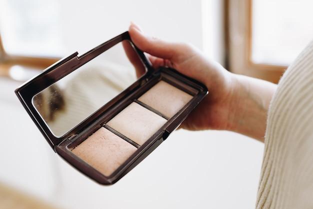 Cerca de la mano del artista de maquillaje profesional o mua está sosteniendo una paleta de cosméticos de sombra de ojos. mujer caucásica con la sombra compacta.