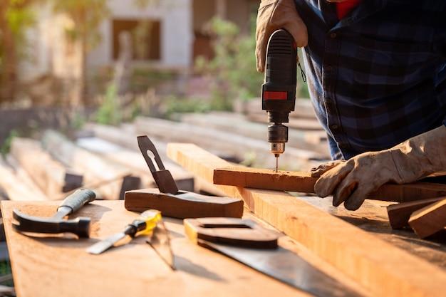 Cerca de la mano del carpintero taladra un agujero de madera con un taladro eléctrico.