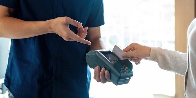 Cerca de la mano del cliente pagando con tarjeta de crédito sin contacto