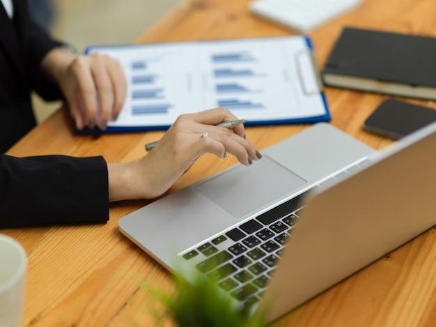 Cerca de la mano empresaria trabajando en equipo portátil con diagrama de información de gráfico de negocios