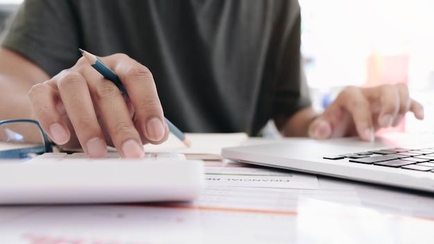 Cerca de la mano del empresario o contador que sostiene la pluma trabajando en la calculadora para calcular datos comerciales, documentos contables y computadora portátil en la oficina, concepto de negocio