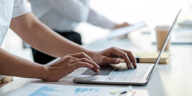 Cerca de la mano del empresario o contador sosteniendo un lápiz trabajando en la calculadora para calcular el informe de datos financieros, documento de contabilidad y computadora portátil en la oficina, concepto de negocio