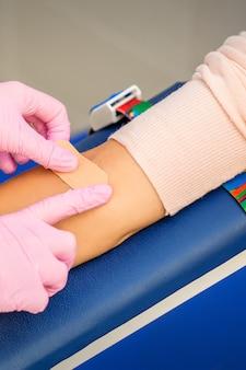 Cerca de la mano de la enfermera aplicando yeso adhesivo en el brazo del paciente después de la extracción de sangre en el hospital