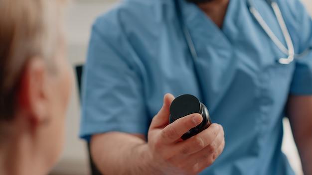 Cerca de la mano de la enfermera sosteniendo una botella de píldoras y cápsulas