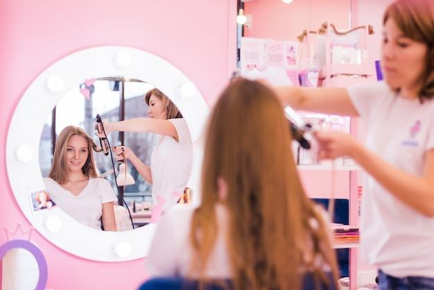 Cerca de la mano del estilista con rizador trabajando para cabello de cliente mujer en salón
