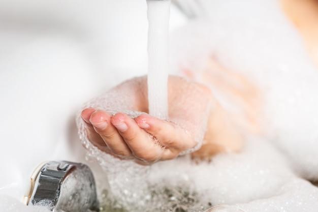Cerca de la mano femenina en espuma de jabón fue sustituida debajo de la corriente