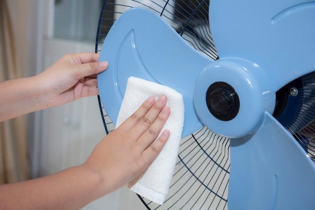 Cerca de la mano femenina que limpia la aspa del ventilador eléctrico sucio con un paño blanco