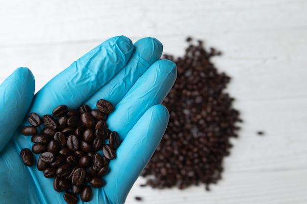 Cerca de la mano en el guante azul con granos de café asado