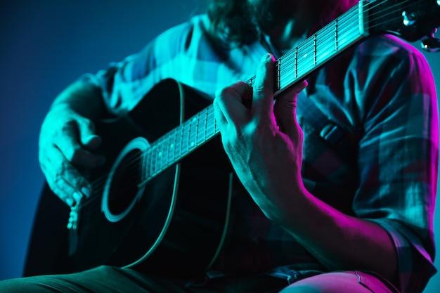 Cerca de la mano del guitarrista tocando la guitarra copyspace macro shot