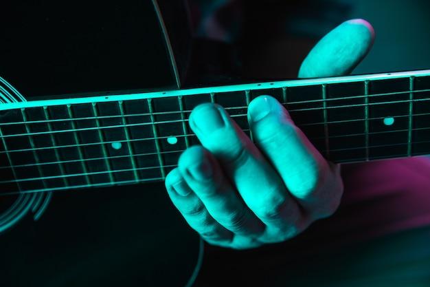 Cerca de la mano del guitarrista tocando la guitarra, copyspace, macro shot