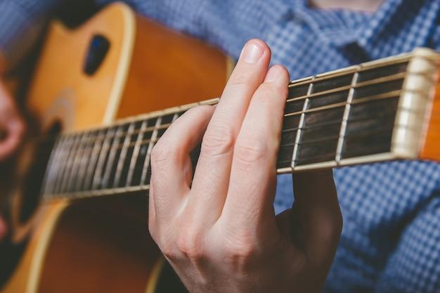 Cerca de la mano del guitarrista tocando la guitarra