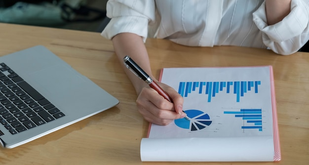 Cerca de la mano del hombre de negocios o del contador que sostiene la pluma que trabaja en la calculadora para calcular los datos comerciales, el documento contable y la computadora portátil en la oficina, concepto del negocio.