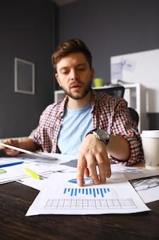Cerca de la mano del hombre de negocios trabajando en una computadora portátil con diagrama de información de gráfico de negocios en un escritorio de madera como concepto