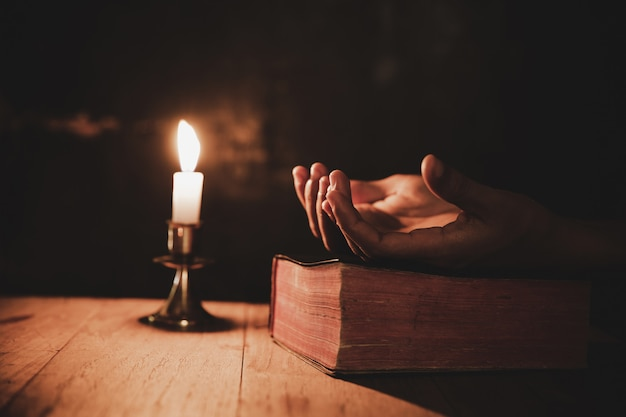 Cerca de la mano del hombre está orando en la iglesia con una vela encendida