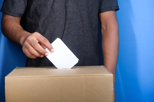 Cerca de la mano del hombre poniendo la tarjeta en la caja con ranura,