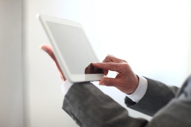 De cerca. la mano de un hombre presiona la pantalla de una tableta digital.