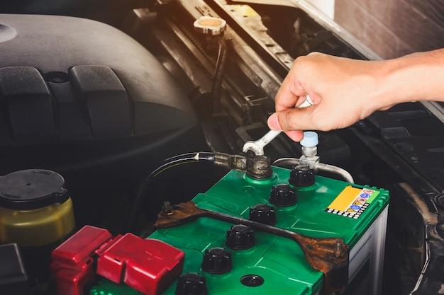 Cerca de la mano del ingeniero mecánico cambiando la batería del coche con una llave