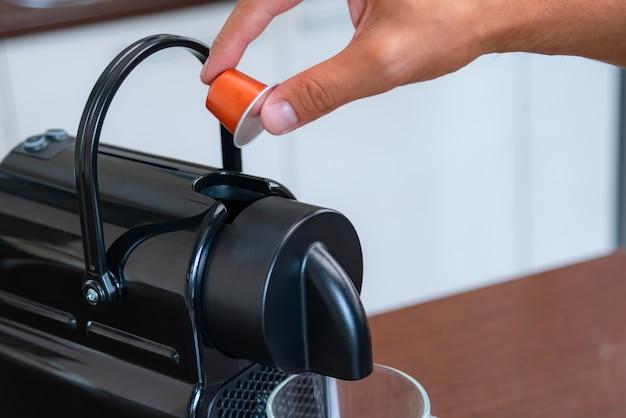 Cerca de la mano insertando una cápsula en una máquina de café