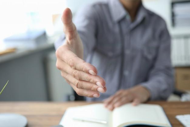 Cerca de la mano masculina para un apretón de manos en la oficina