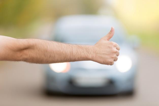 Cerca de la mano masculina de autostop