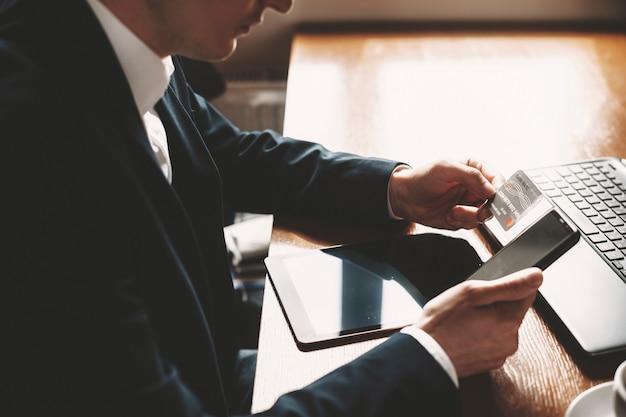Cerca de una mano masculina con una tarjeta de crédito y un teléfono inteligente para operaciones en línea en un restaurante.