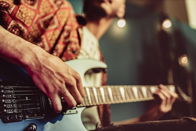 Cerca de la mano masculina tocando la guitarra eléctrica en la oscuridad