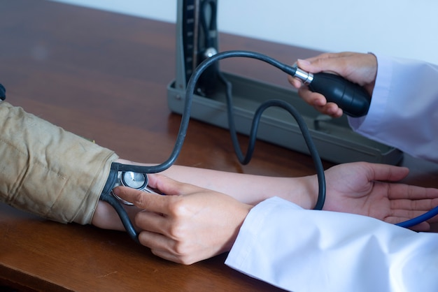 Cerca de la mano del médico y el paciente mediante el control de medición de la presión arterial