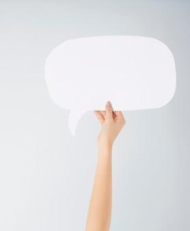 Cerca de la mano de la mujer con burbujas de discurso