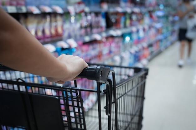 Cerca de la mano de la mujer empujando un carrito de compras en una tienda de supermercado.