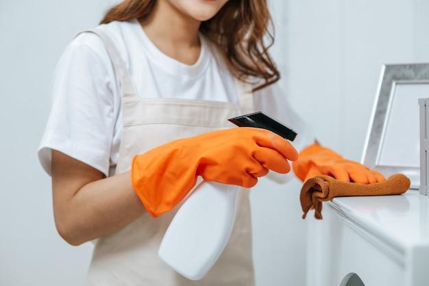 Cerca de la mano de la mujer joven ama de llaves con guantes de goma use una solución de limpieza en una botella de spray sobre muebles blancos y use un paño para limpiarlo