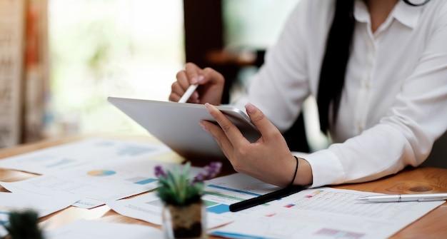 Cerca de la mano de la mujer o del contador que sostiene la pluma que trabaja en la computadora portátil para calcular los datos comerciales, el documento de contabilidad y la calculadora en la oficina, el concepto de negocio
