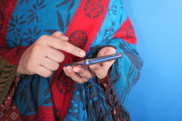 Cerca de la mano de la mujer sosteniendo un teléfono inteligente.